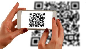 A person scanning a QR Code using a smartphone - QR codes are an ideal way to get more reviews